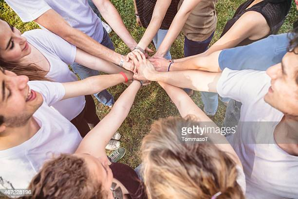 teamwork - friends in a huddle with hands stacked - sports team event stock photos and pictures