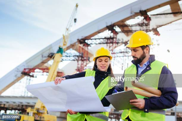 teamwork in construction industry - two engineers working together on construction site with blueprints and plans - bridge built structure stock pictures, royalty-free photos & images