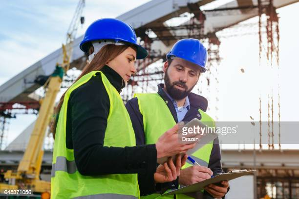 teamwork in construction industry - two engineers working together on construction site with blueprints and plans - civil engineering stock pictures, royalty-free photos & images