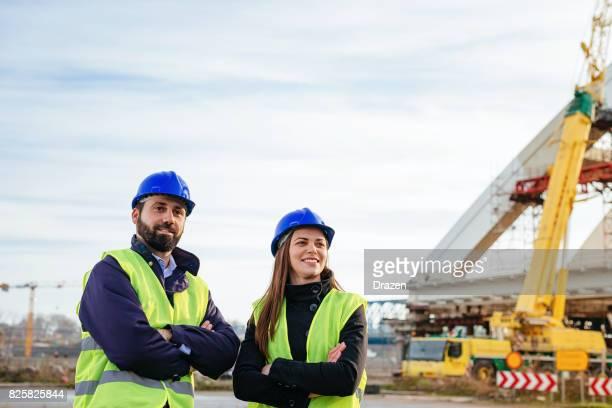 Trabajo en equipo en la industria de la construcción - dos ingenieros que trabajan juntos en el sitio de construcción con planos y planes