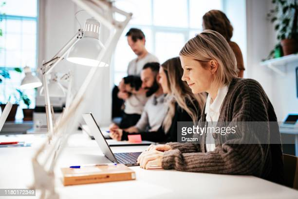 teamwork in modern coworking space - office stock pictures, royalty-free photos & images