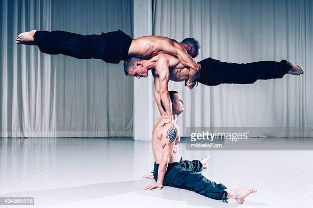 teamwork is a succes as acrobats use strength and balance - acrobatic activity stock photos and pictures