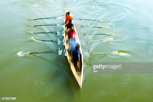 Teamwork, motion blurred rowers in rowing boat training on river