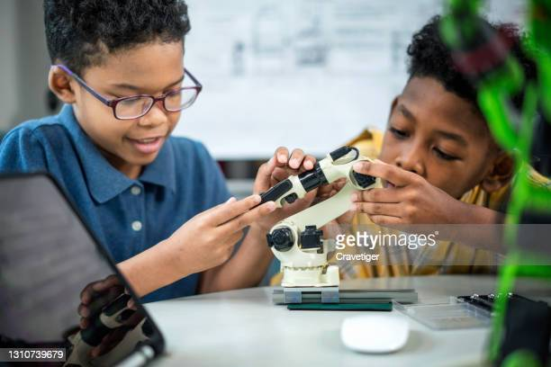 teamwork of children during assembly  and simulate robot with coding it for present in classroom. - stem stock pictures, royalty-free photos & images