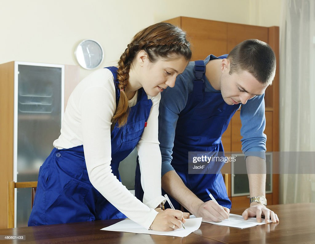 Teamwork of workers  filling in questionnaire : Stock Photo