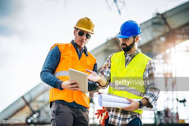 Teamwork on construction site with two engineers