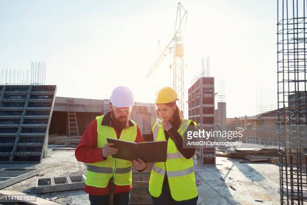 teamwork on construction site working on building construction, woman architect and man on middle age working together on construction site - civil engineering stock pictures, royalty-free photos & images