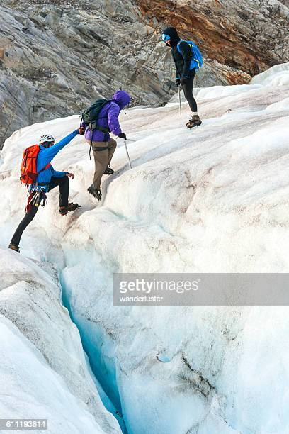 teamwork on the icy glacier - crevasse stock photos and pictures