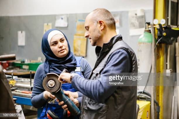 teamwork: technician explains a grinder to a female trainee in a workshop - trainee stock pictures, royalty-free photos & images