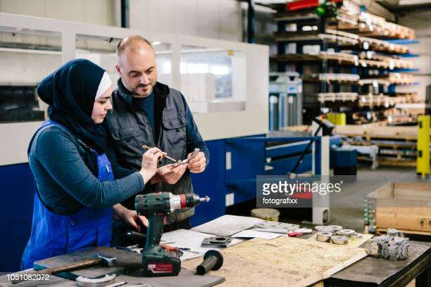 teamwork: technician explains a work tool to a young woman in a workshop - emigration and immigration stock pictures, royalty-free photos & images