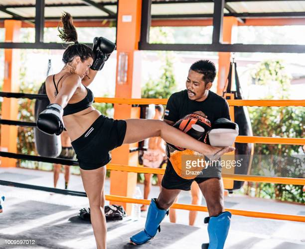 teamwork with personal trainer in muay thai camp in thailand - young woman using elbow punch - muay thai imagens e fotografias de stock