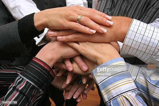 Teamwork Zusammenarbeit Zusammenhalt Teamgeist Solidaritaet uebereinandergelegte Haende