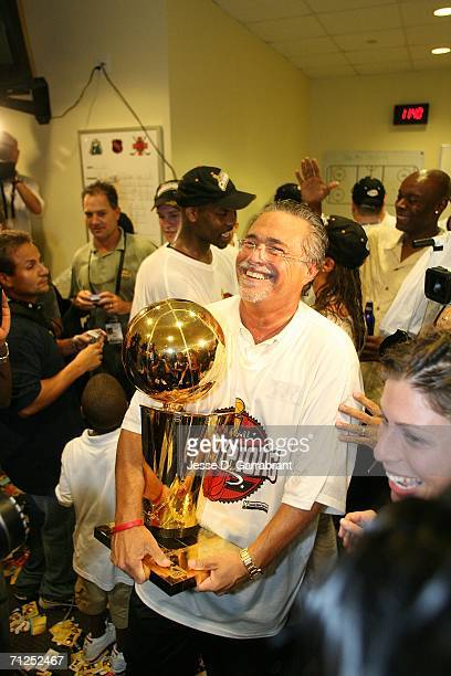 Tean owner Micky Arison of the Miami Heat celebrates with the Larry O'Brien trophy in the locker room after they won the NBA Championship with their...