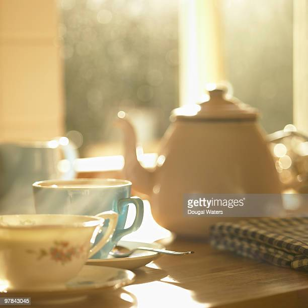Teapot and cups in kitchen.