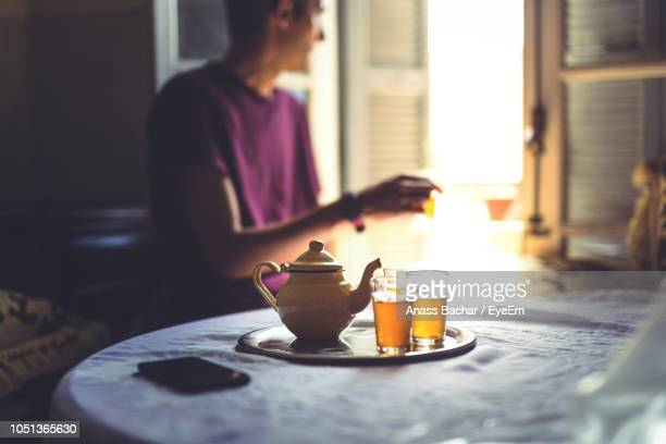 Teapot And Drinks On Table With Man Sitting In Background