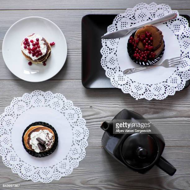 teapot and plates of dessert on lace doilies - doily stock photos and pictures