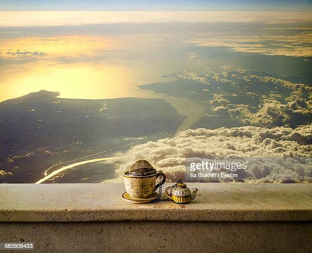 Teapot And Tea Cup On Railing Against Sea At Sunset