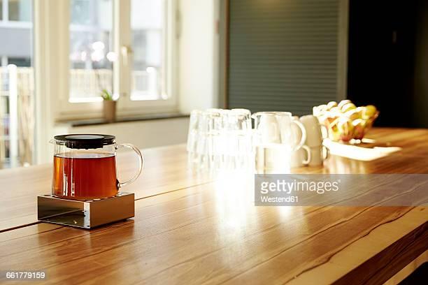 Teapot on teapot warmer on tabletop in a modern office
