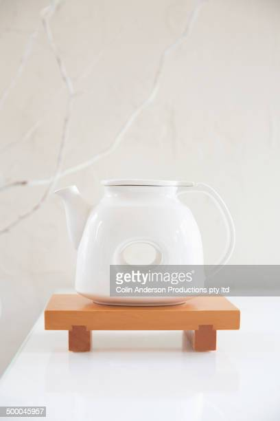 Teapot on wooden stand on table