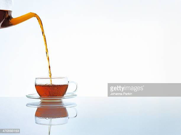 Teapot pouring tea into glass cup and saucer