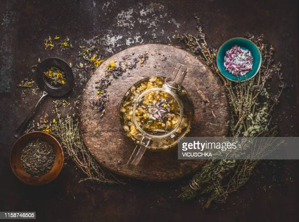 teapot with herbal tea on dark background with medicinal herbs and flowers - herbal tea stock pictures, royalty-free photos & images