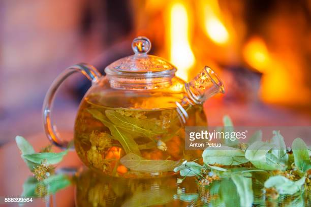 Teapot with lime tea and linden flowers on the background of the fireplace