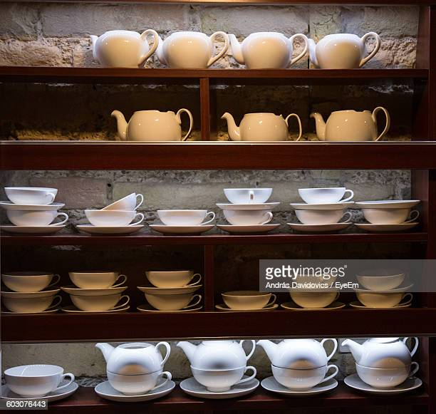 Teapots And Cups Displayed In Shelves For Sale