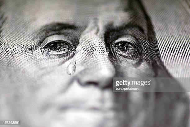 Tear falling from face on US dollar bill, close-up