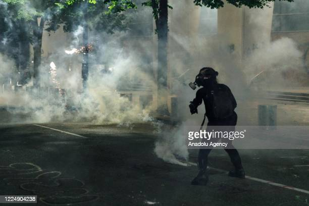 Tear gas and fireworks mix as Black Lives Matter supporters demonstrate in Portland, Oregon on July 4, 2020 for the thirty-eighth day in a row at...
