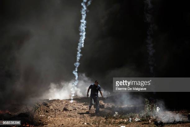 A tear gas canister falls near a Palestinian at the border fence with Israel as mass demonstrations continue on May 14 2018 in Gaza City Gaza Israeli...