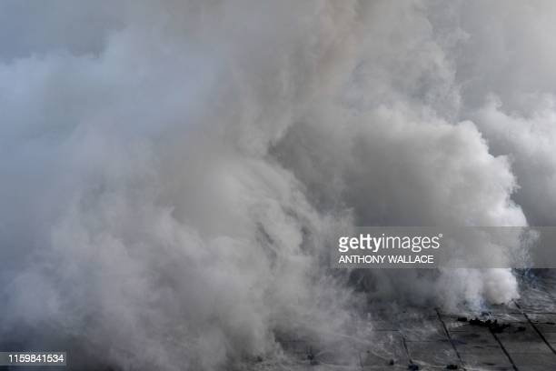 Tear gas fired by the police in an attempt to disperse protesters is seen in the Admiralty area during a general strike in Hong Kong on August 5 as...