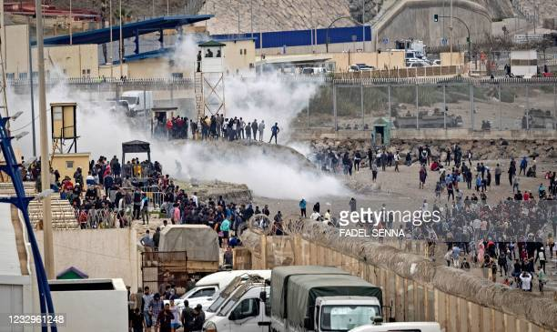 Tear gas fumes fill the air as Moroccan migrants rally by a border fence in the northern town of Fnideq in an attempt to cross the border from...