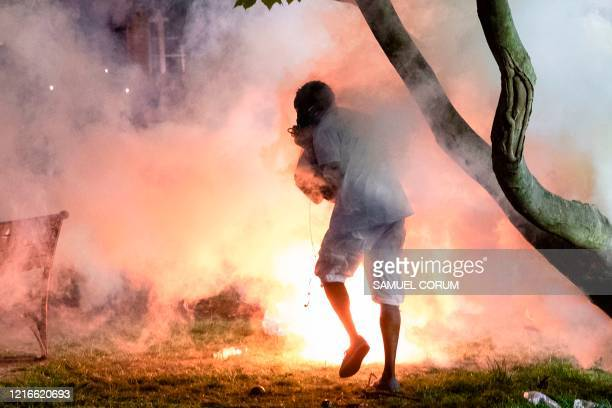 Tear gas goes off near a man as demonstrators and police face off in front of the White House during a protest against the death of George Floyd at...