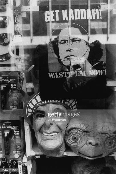 Tear gas handcuffs masks of Ronald Reagan and 'ET The ExtraTerrestrial' and a poster of Libyan leader Muammar Gaddafi displayed in a shop window on...