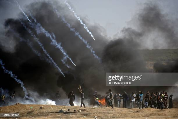 TOPSHOT Tear gas is fired at protestors during clashes with Israeli forces near the border between the Gaza strip and Israel east of Gaza City on May...