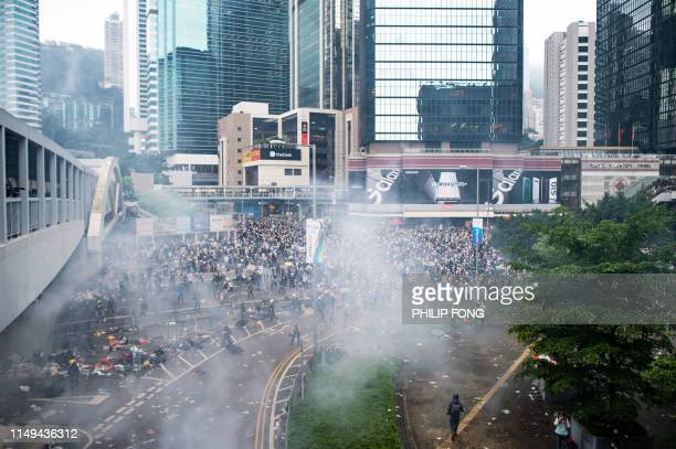 Tear gas is seen outside the Legislative Council during violent clashes between police and protesters rallying against a controversial extradition...
