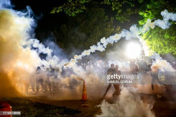 TOPSHOT Tear gas rises above as protesters face off with police during a demonstration outside the White House over the death of George Floyd at the...