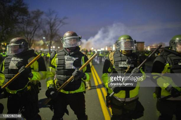 Tear gas rises from behind a line of Minnesota State Troopers as they block the road from anyone going back towards the Brooklyn Center police...