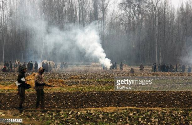 Tear smoke rises as Indian policemen move near the encounter site in Pinglena area of Pulwama some 30 kilometers from Srinagar Kashmir on February 18...