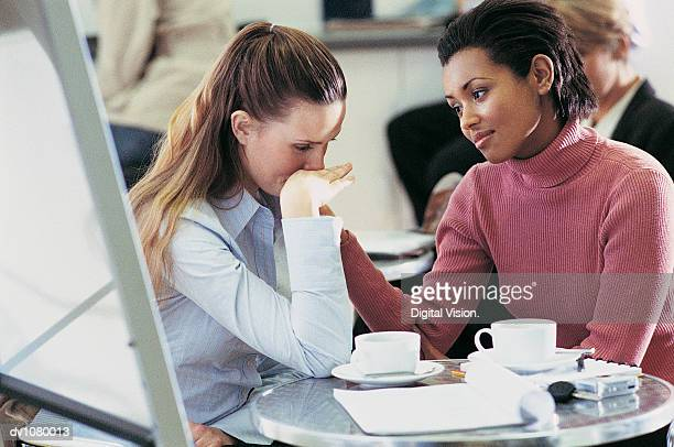 tearful businesswoman being consoled by a colleague sitting at a table in an office canteen - hand on shoulder stock photos and pictures