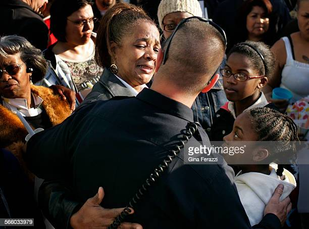 A tearful Denise Cusseaux–Vital of Oakland with her daughter Tamara gets a hug from Oakland Police Officer Tim Scarrott at the beginning of a candle...