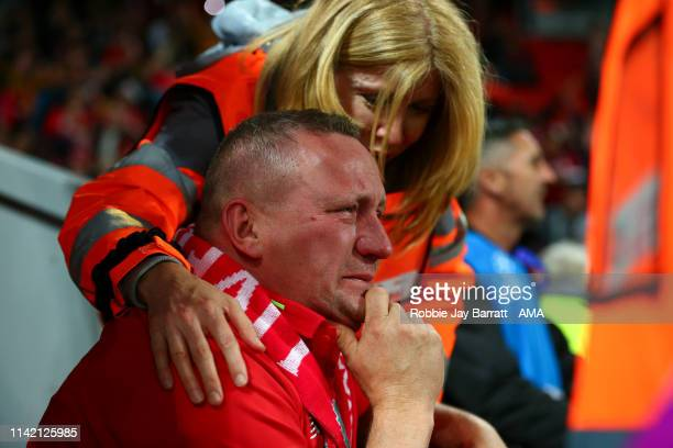 A tearful fan of Liverpool is consoled by a steward at full time during the UEFA Champions League Semi Final second leg match between Liverpool and...
