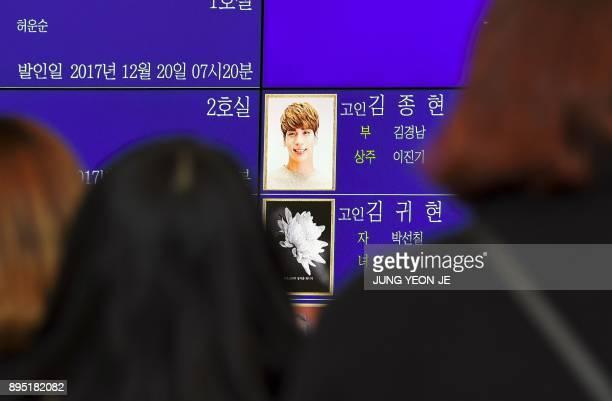 Tearful fans watch the portrait of Kim JongHyun a 27yearold lead singer of the massively popular Kpop boyband SHINee on an electronic board outside a...