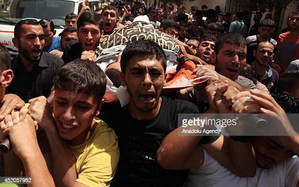 Tearful relatives of Mohammed Sweilem, killed in an Israeli airstrike staged to Jabalia Refugee Camp, attend the funeral ceremony on July 12, 2014 in...