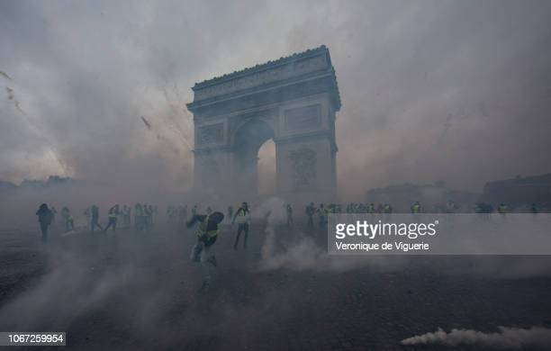 Teargas surrounds protesters as they clash with riot police during a 'Yellow Vest' demonstration near the Arc de Triomphe on December 1 2018 in Paris...