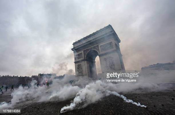 Teargas surrounds riot police as they clash with protesters during a 'Yellow Vest' demonstration near the Arc de Triomphe on December 1 2018 in Paris...