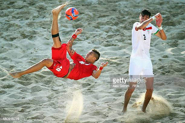 Tearii Labaste of Tahiti does a bicycle kick next to Amir Akrabi of Iran during the FIFA Beach Soccer World Cup Portugal 2015 Quarterfinal match...