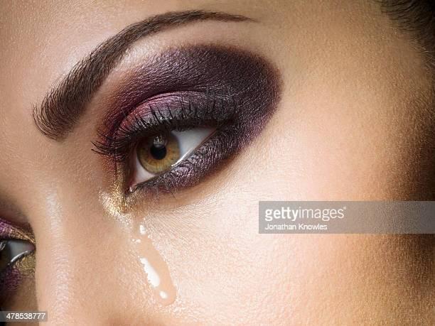 Tears down female face, strong eye make up