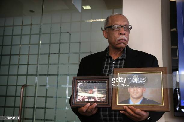 Tears roll down the face of retired Chicago police officer Thomas Wortham III as he holds pictures of his son while listening to his wife speak...