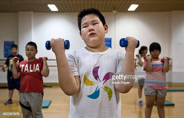 Tears run down the cheeks of an overweight Chinese student as he uses weights during training at a camp held for overweight children at a local...